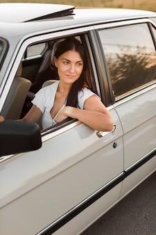 Mittlere schussfrau, die altes auto fährt