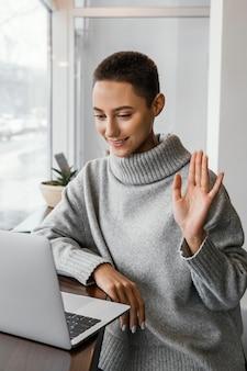Mittlere schussfrau, die am laptop winkt
