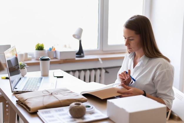 Mittlere schussfrau, die am schreibtisch arbeitet