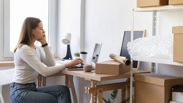 Mittlere schussfrau, die am schreibtisch sitzt