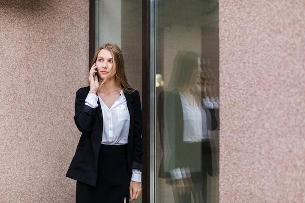 Mittlere schussfrau, die am telefon am fenster spricht