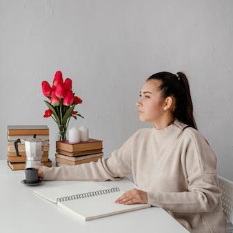 Mittlere schussfrau, die am tisch sitzt