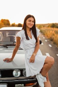Mittlere schussfrau, die auf auto aufwirft
