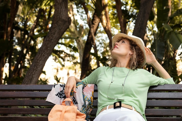 Mittlere schussfrau, die auf bank sitzt