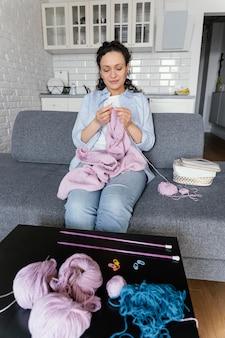 Mittlere schussfrau, die auf couch strickt