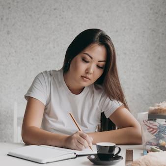 Mittlere schussfrau, die auf notizbuch schreibt