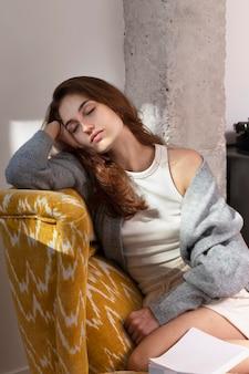 Mittlere schussfrau, die auf sessel schläft