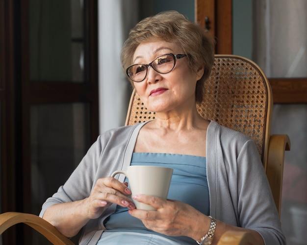 Mittlere schussfrau, die auf stuhl sitzt