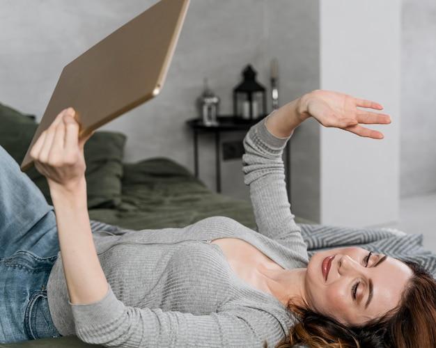 Mittlere schussfrau, die auf tablette winkt