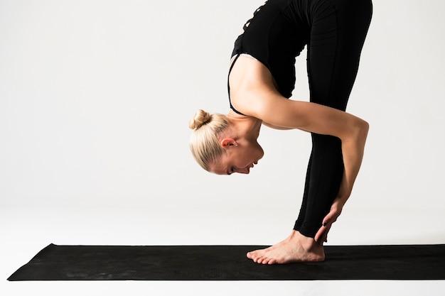 Mittlere schussfrau, die auf yogamatte steht