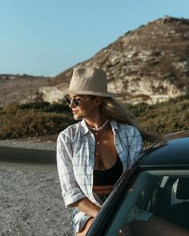 Mittlere schussfrau, die aus autofenster am strand steht