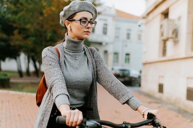 Mittlere schussfrau, die das fahrrad reitet