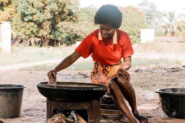 Mittlere schussfrau, die draußen kocht