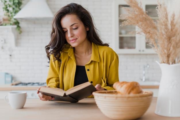 Mittlere schussfrau, die ein buch am tisch liest