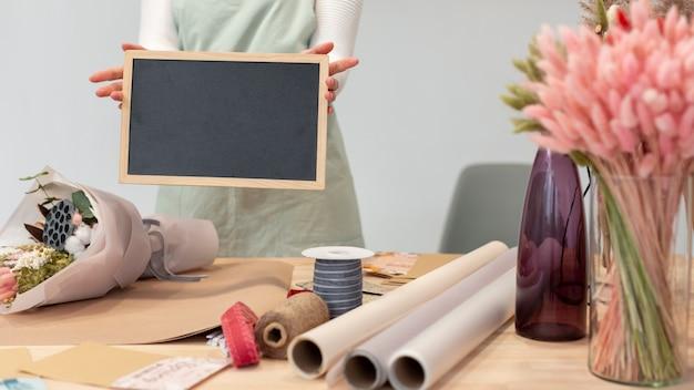 Mittlere schussfrau, die eine leere kopierraumtafel hält