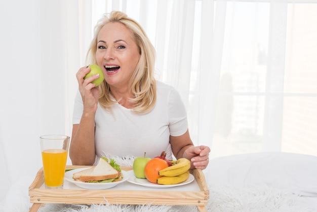 Mittlere schussfrau, die einen apfel isst