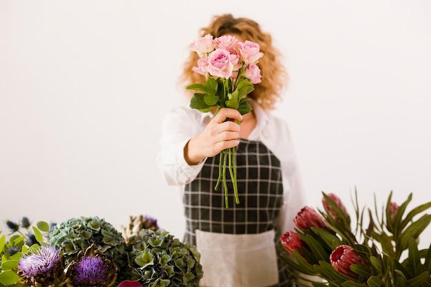 Mittlere schussfrau, die einen blumenstrauß von rosen hält