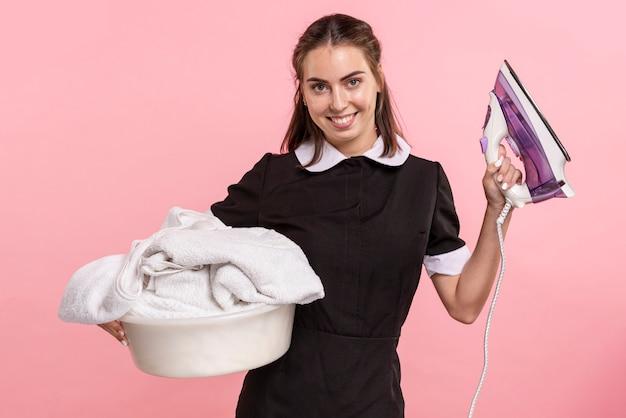 Mittlere schussfrau, die einen wäschekorb und ein eisen hält