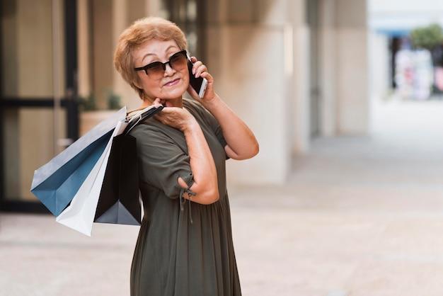 Mittlere schussfrau, die einkaufstaschen hält