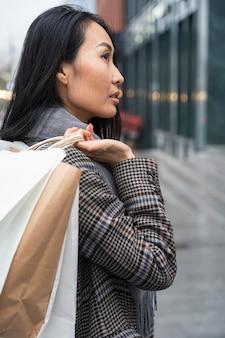 Mittlere schussfrau, die einkaufstaschen trägt