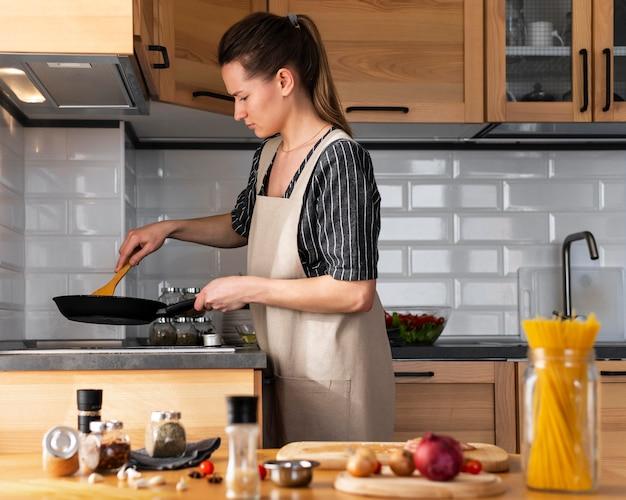 Mittlere schussfrau, die essen zubereitet