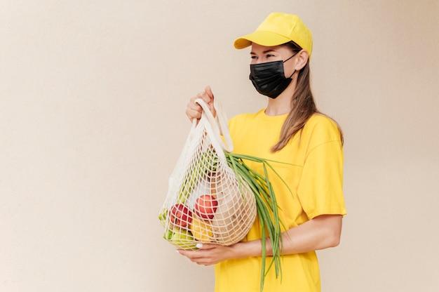 Mittlere schussfrau, die fruchtnetz hält