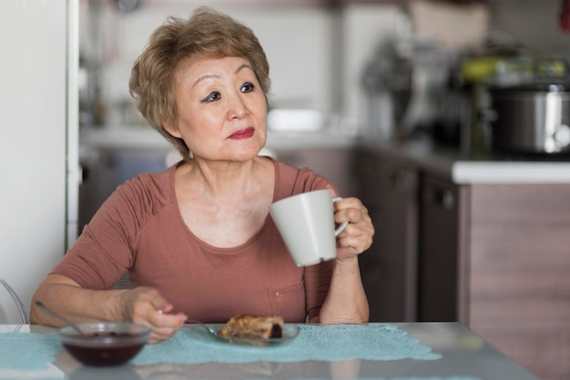 Mittlere schussfrau, die frühstück nimmt