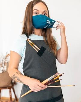 Mittlere schussfrau, die gemalte maske trägt