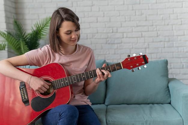 Mittlere schussfrau, die gitarre spielt