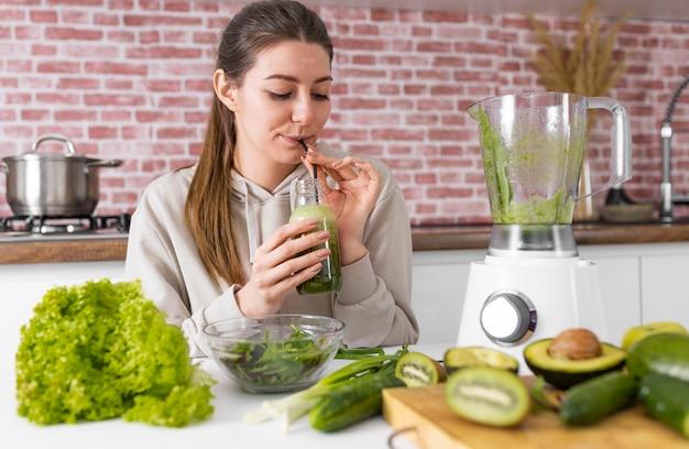 Mittlere schussfrau, die grünen smoothie trinkt
