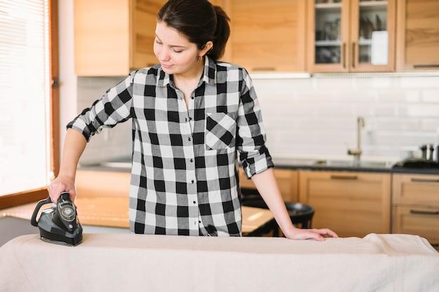 Mittlere schussfrau, die handtuch bügelt