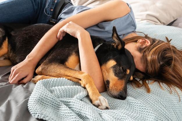 Mittlere schussfrau, die hund im bett umarmt
