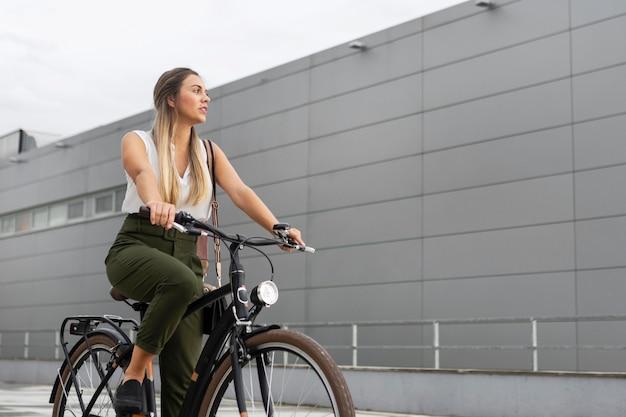 Mittlere schussfrau, die ihr fahrrad reitet