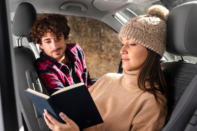 Mittlere schussfrau, die im auto liest