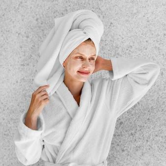 Mittlere schussfrau, die im bademantel aufwirft