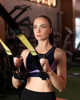 Mittlere schussfrau, die im fitnessstudio trainiert