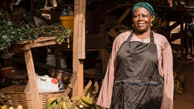 Mittlere schussfrau, die im markt arbeitet