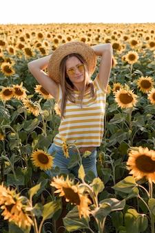Mittlere schussfrau, die im sonnenblumenfeld aufwirft