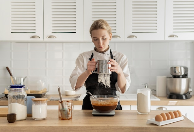 Mittlere schussfrau, die in der küche kocht