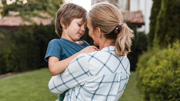 Mittlere schussfrau, die jungen umarmt