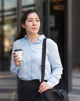 Mittlere schussfrau, die kaffee hält