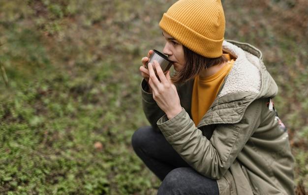 Mittlere schussfrau, die kaffee im wald trinkt