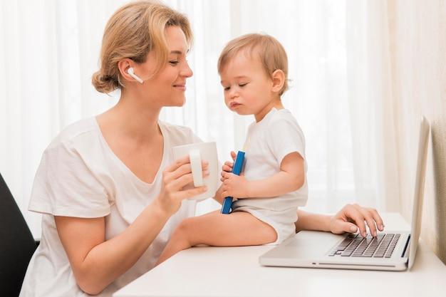 Mittlere schussfrau, die kaffee und baby auf schreibtisch trinkt
