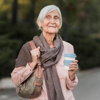 Mittlere schussfrau, die kaffeetasse hält