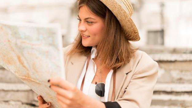 Mittlere schussfrau, die karte betrachtet