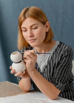 Mittlere schussfrau, die keramikgegenstand malt
