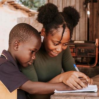 Mittlere schussfrau, die kind lehrt, zu schreiben