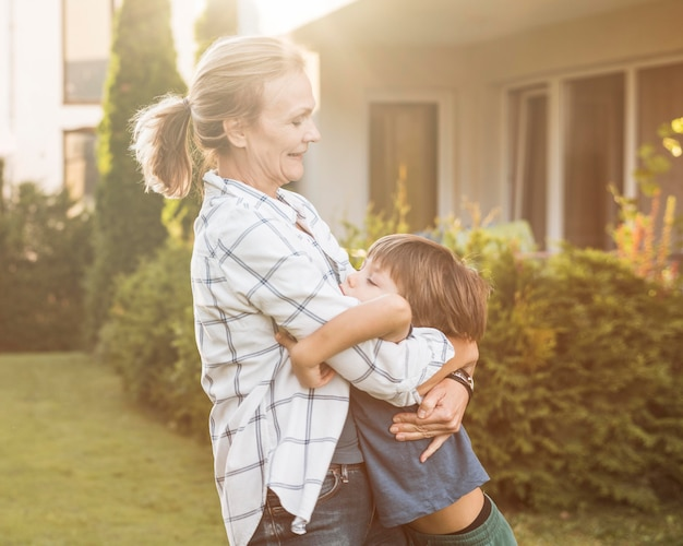 Mittlere schussfrau, die kind umarmt
