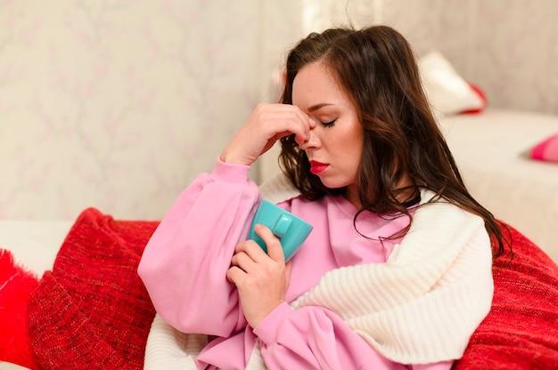 Mittlere schussfrau, die kopfschmerzen hat