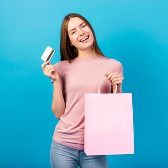 Mittlere schussfrau, die kreditkarte und tasche hält